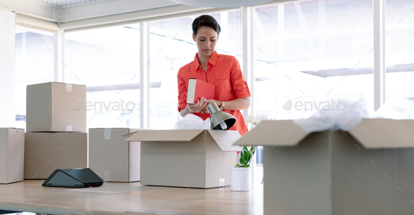 Caucasian businesswoman unpacking office belongings from cardboard boxes on table - Stock Photo - Images