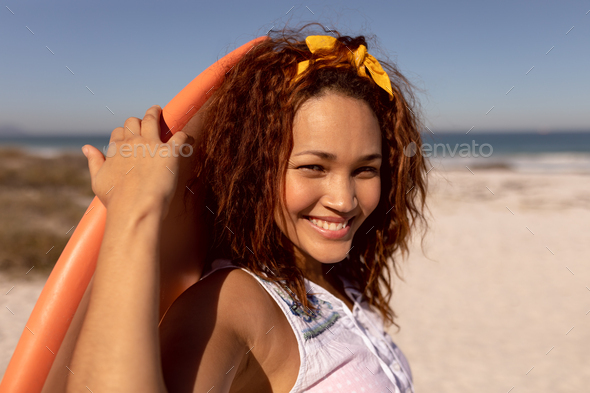 Beautiful happy Mixed-race woman with surfboard looking at camera on beach - Stock Photo - Images