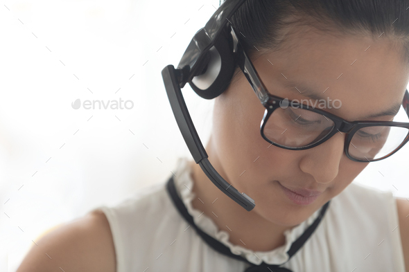 Beautiful Asian female customer service executive with headset looking down - Stock Photo - Images