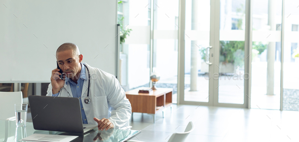 Mixed-race male doctor talking on mobile phone while using laptop at table - Stock Photo - Images