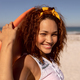 Beautiful happy Mixed-race woman with surfboard looking at camera on beach - PhotoDune Item for Sale