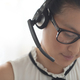 Beautiful Asian female customer service executive with headset looking down - PhotoDune Item for Sale