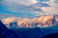 Scenic view of foggy mountains. Sunlit rocks and clouds - PhotoDune Item for Sale