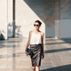 Refined young woman in leather skirt and silk blouse walking confident near a building. - PhotoDune Item for Sale