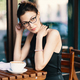 Young stylish woman with stylish glasses sitting at table in cafe with a big cup of coffee or latte - PhotoDune Item for Sale