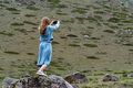 Back view female hiker takes photo of beautiful mountains in North Caucasus - PhotoDune Item for Sale