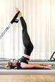 Woman doing short spine pilates exercise - PhotoDune Item for Sale