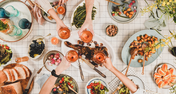 Peoples hands clikning with wineglasses over table with snacks - Stock Photo - Images