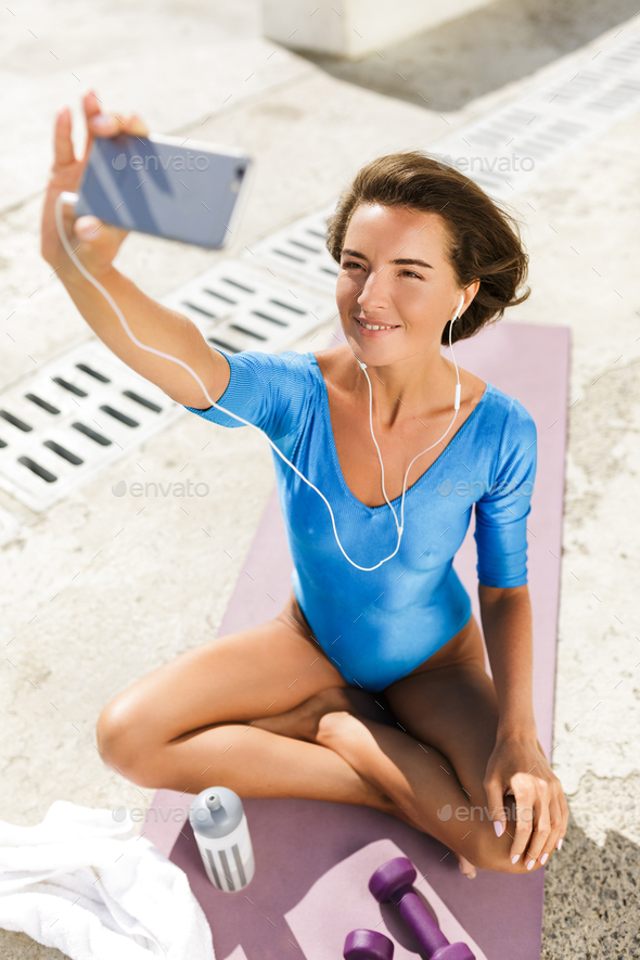 Smiling woman in swimsuit sitting on yoga mat happily looking in cellphone and taking selfie - Stock Photo - Images