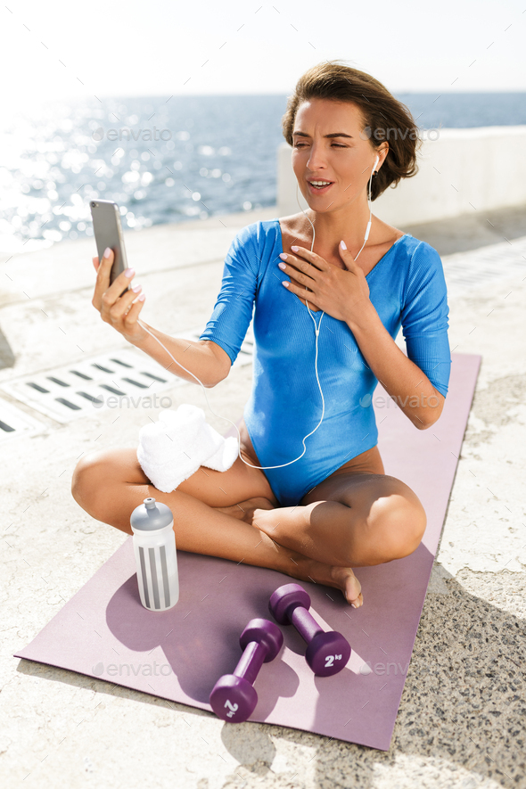 Beautiful woman in swimsuit on yoga mat thoughtfully looking in cellphone and talking by video call - Stock Photo - Images