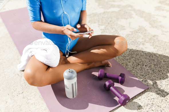 Female body in blue swimsuit sitting on purple yoga mat in lotus pose and holding cellphone in hands - Stock Photo - Images