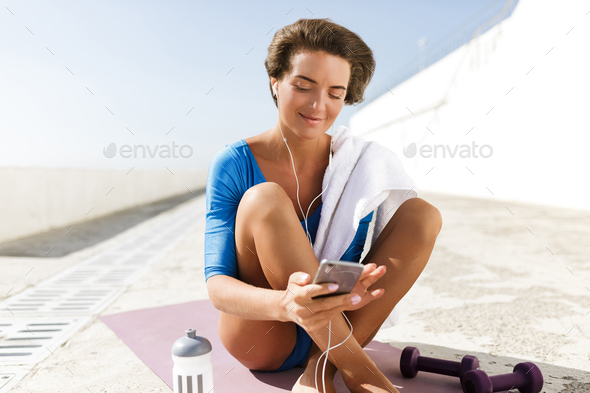 Pretty woman in swimsuit and earphones sitting on purple yoga mat dreamily looking in cellphone - Stock Photo - Images