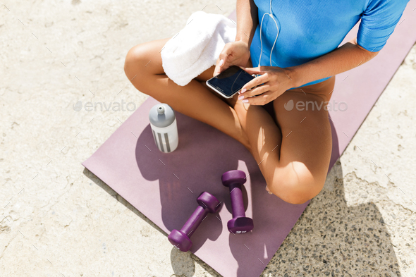 Female body in blue swimsuit sitting on yoga mat in lotus pose and using cellphone - Stock Photo - Images