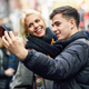 Happy couple of tourists taking selfie in a crowded street - PhotoDune Item for Sale