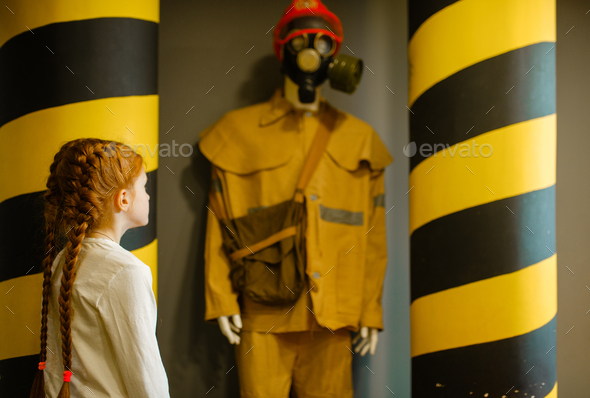Female child looks on fireman mannequin, playroom