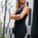 Fit Woman with Arms Crossed Standing Against Futuristic Modern Building In City - PhotoDune Item for Sale