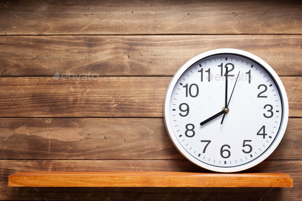 wall clock at shelf on wooden background - Stock Photo - Images