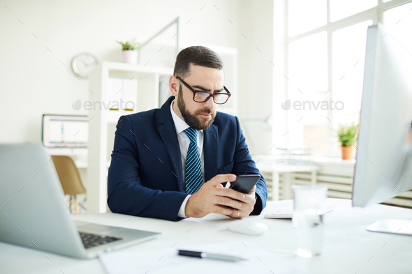 Businessman reading sms in office - Stock Photo - Images