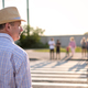 Mature man in summer hat waiting to cross street on sunny day. - PhotoDune Item for Sale