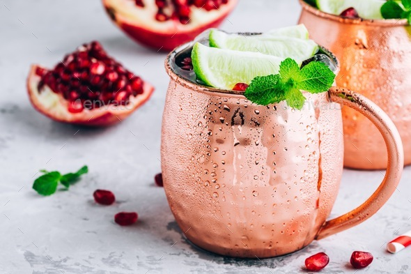 Iced Cold Moscow Mule cocktail with lime and pomegranate - Stock Photo - Images