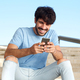happy young man sitting with cellphone - PhotoDune Item for Sale