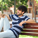 young man smiling with mobile phone in park - PhotoDune Item for Sale