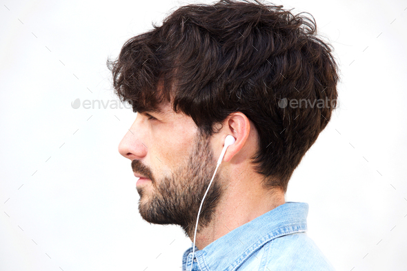 profile portrait of young man with beard listening to music with earphones - Stock Photo - Images