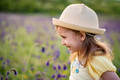 Cute smiling baby girl in beige hat outdoors in green field. Child portrait - PhotoDune Item for Sale