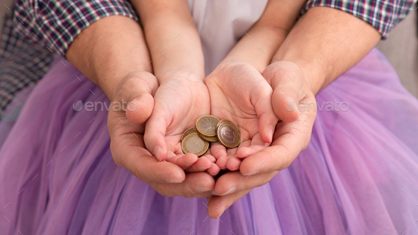 Dad and his daughter holding coins in hands together