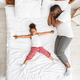 Little african girl lying like star on big parent bed, her daddy on side - PhotoDune Item for Sale