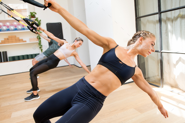 Class doing Trx power pull exercises in a gym - Stock Photo - Images