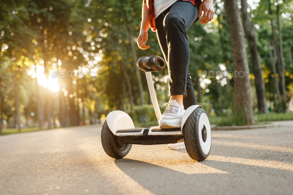 Young male person riding on gyroboard in park - Stock Photo - Images