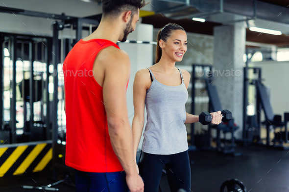 Young adult woman working out in gym with trainer - Stock Photo - Images