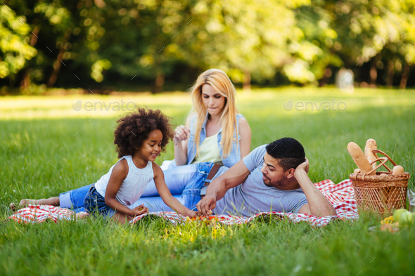 Picture of lovely couple with their daughter having picnic - Stock Photo - Images