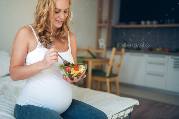 Portrait of pregnant woman eating healthy food - Stock Photo - Images