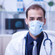 Portrait of serious doctor wearing a protection mask over his mouth - PhotoDune Item for Sale