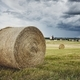 Straw bales stacked on field against storm - PhotoDune Item for Sale