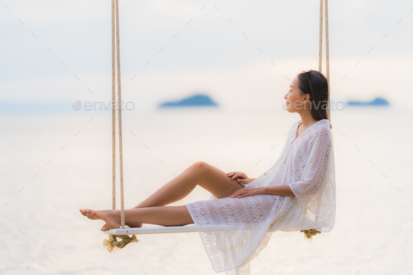 Portrait beautiful young asian woman sitting on the swing around - Stock Photo - Images
