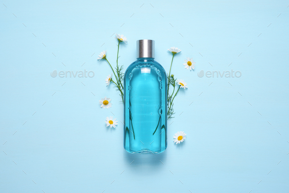 Cosmetic bottle and chamomile flowers on blue table top view - Stock Photo - Images