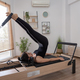 Young woman exercising on pilates reformer bed - PhotoDune Item for Sale