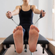 Young woman exercising on pilates reformer bed, feet close up - PhotoDune Item for Sale