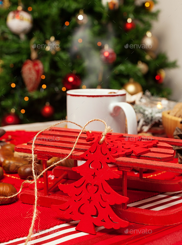 Cup of hot tea on with behind christmas tree. - Stock Photo - Images