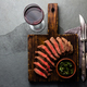 Slices of beef medium rare steak on wooden board, glass of red wine on slate background - PhotoDune Item for Sale