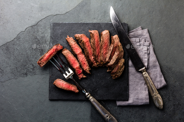 Medium rare beef steak on slate board, vintage cutlery, grey background - Stock Photo - Images