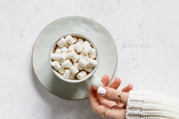 Girl's hand holds a cup of hot chocolate with marshmallow over textured white background - Stock Photo - Images