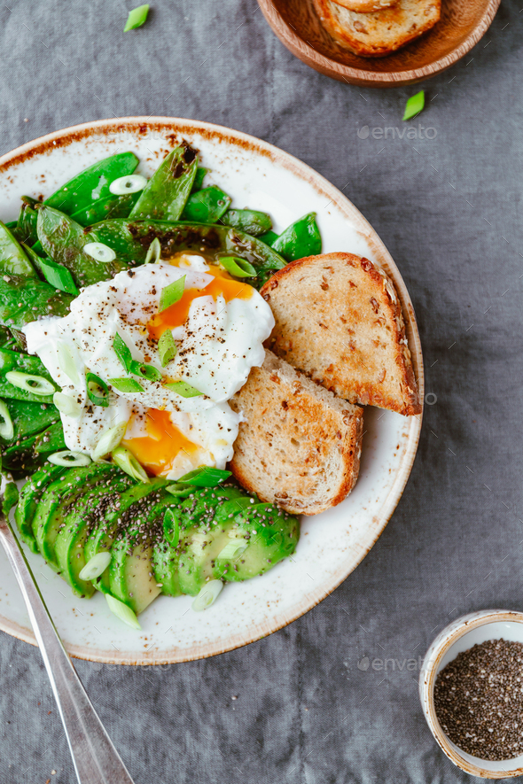 Fried snow peas, avocado, poached eggs are sprinkled chia seeds with toasts - Stock Photo - Images