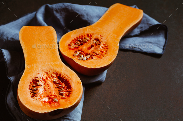 View on raw halves of butternut squash on a kitchen table - Stock Photo - Images