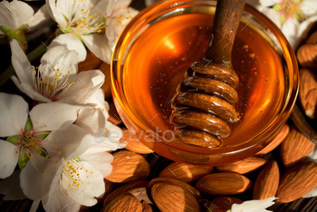 Almond honey, nuts and white flowers close