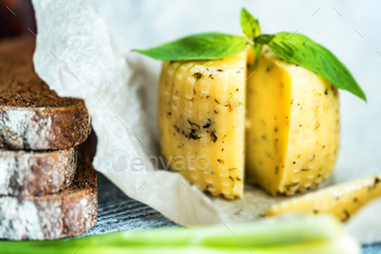 Rustic cheese with herbs on paper and vegetables
