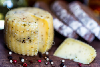 Rustic cheese with herbs, rye bread and peppercorn